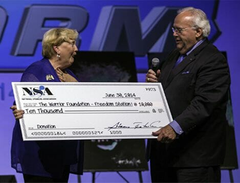 Elderly woman gratefully receiving a large check for $10,000 from the NSA Foundation